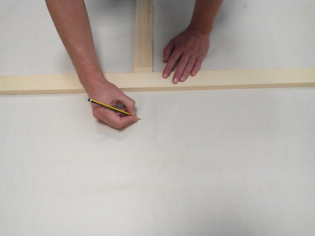 Si sobra tela medimos la cantidad de tela que necesitamos para que cubra el listón del bastidor y cortamos.